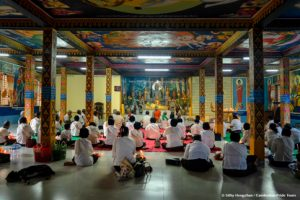 Buddhist followers repeat the pray after monk