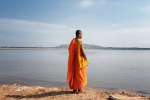 Buddhist monk standing by the Mekong River