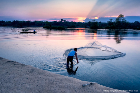 Cambodia fisherman throwing net to catch fish in the Mekong River