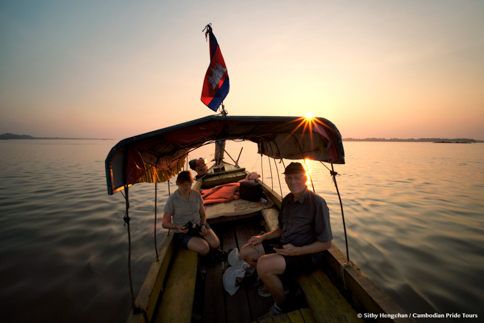 Couple on Mekong boat cruise to see dolphins during sunset