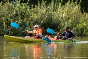 Family kayaking through Mekong flooded forests of Ramsar Wetlands