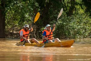 Father and son kayaking through beautiful Mekong flooded forests of Ramsar Wetlands in monsoon season