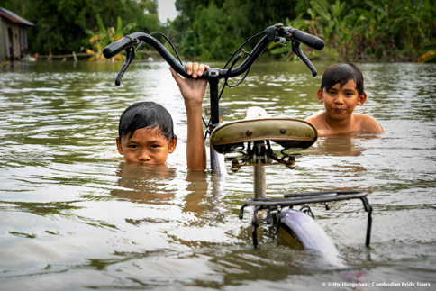 Local kids swimming with their bike cycle in Mekong flood during monsoon in Cambodia