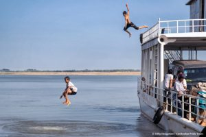Boys jumping off the ferry roof top into river