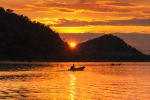Mekong sunset and fisherman driving his boat