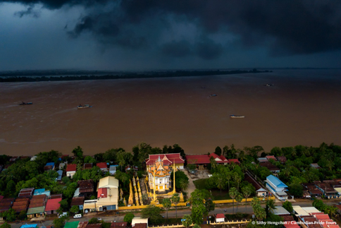Storm cloud over Mekong river and sand collecting boat Kratie Cambodia