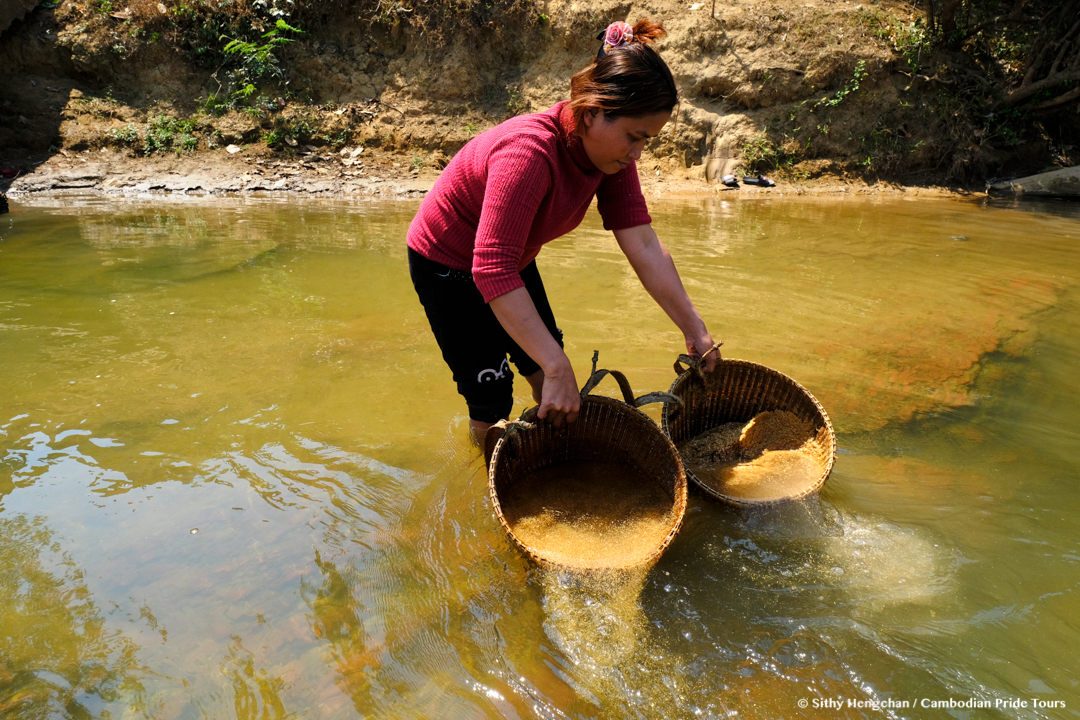 Indigenous woman cleaning rice in Sesan River to make white wine
