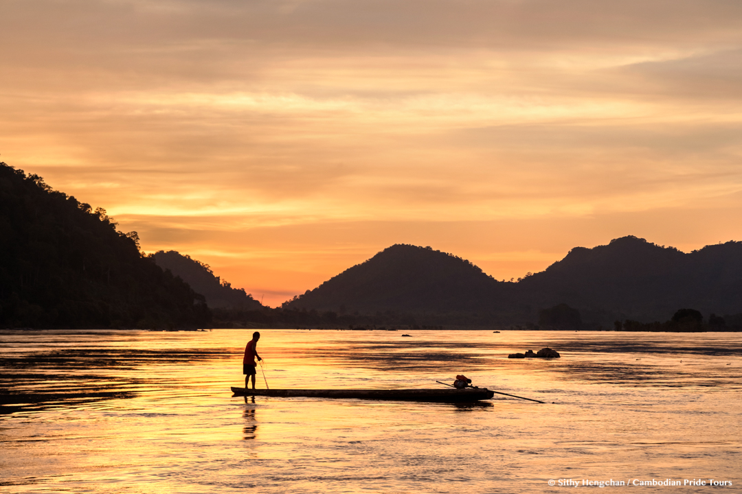 Local fisherman collecting fish in the Mekong river during sunset