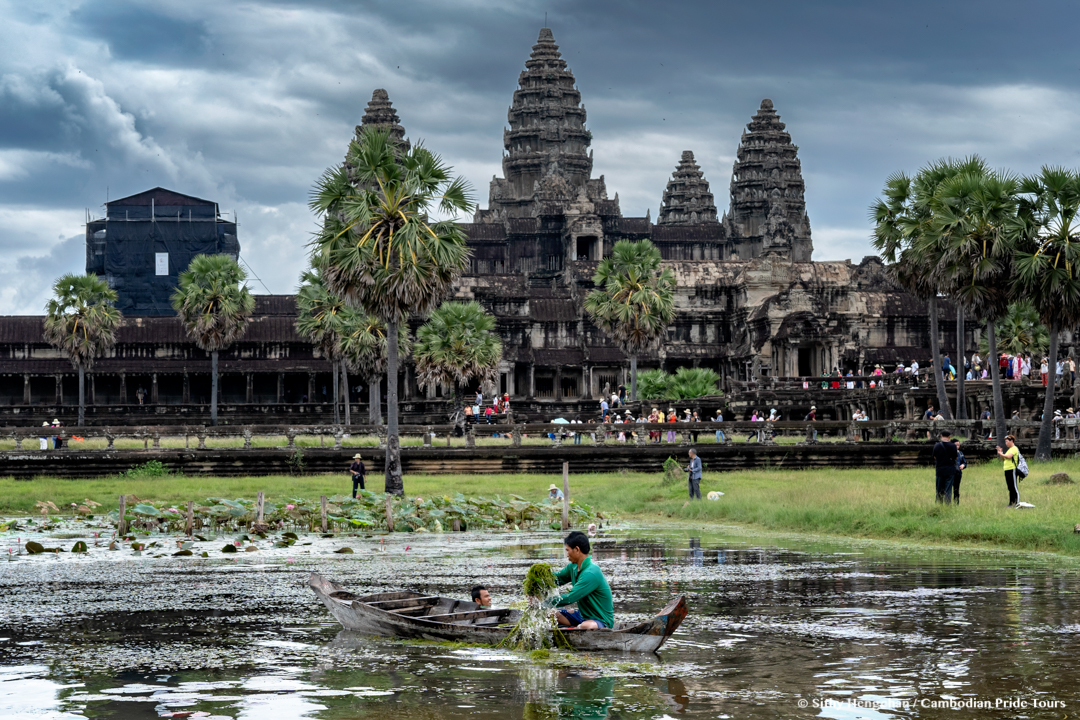 Workers clearing grass from pond in front of Angkor Wat