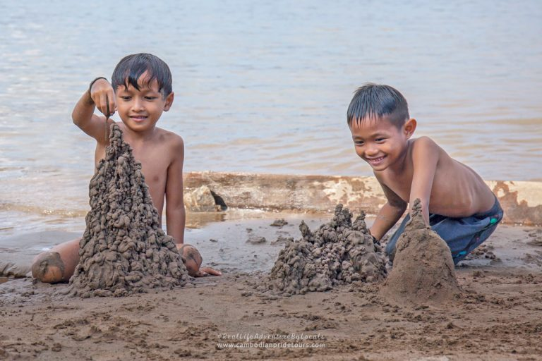 Kids building sand-castle by the Mekong