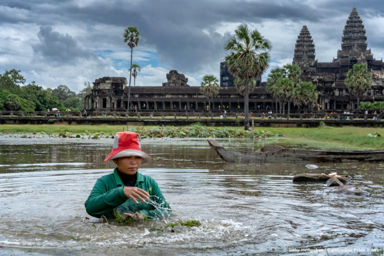 Workers clearing the grass from pond in front of Angkor Wat Temple